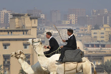 Egyptian policemen patrol on camels near the Giza Pyramids near Cairo, Egypt, Saturday, Dec. 3, 2011. (AP Photo/Bela Szandelszky)