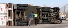 Steve Griffin  |  The Salt Lake Tribune A motorist and Utah Highway Patrol trooper run to a semitractor trailer that had just been blown over by high winds near Farmington Thursday.