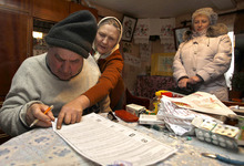Russians fill their ballot papers at a home in the village of Oster, 380 kilometers (237 miles) west of Moscow, Sunday, Dec. 4, 2011. Russians cast their ballots with muted enthusiasm in national parliamentary elections Sunday, a vote that opinion polls indicate could water down the strength of the party led by Prime Minister Vladimir Putin, despite the government's relentless marginalization of opposition groups. (AP Photo/Sergei Grits)
