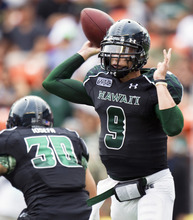 Hawaii running back Joey Iosefa (30) protects quarterback David Graves' (9) blind side as Graves throws a pass to Hawaii wide receiver Trevor Davis for a touchdown in the second quarter of an NCAA college football game on Saturday, Dec. 3, 2011, in Honolulu. (AP Photo/Eugene Tanner)