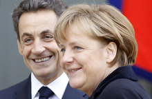 French President Nicolas Sarkozy, left, smiles as he greets German Chancellor Angela Merkel prior to their meeting at the Elysee Palace in Paris, Monday Dec. 5, 2011. The leaders of Germany and France will try to agree Monday on a cohesive plan to help save the euro through stricter oversight of government budgets. Financial markets signaled optimism that French President Nicolas Sarkozy and German Chancellor Angela Merkel will unveil a unified plan that tightens political and economic cooperation among the 17 European Union countries that use the euro and sets the stage for more aggressive aid from the European Central Bank. (AP Photo/Remy de la Mauviniere)