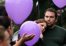 Susan Powell's sister Denise Cox, leans on her fiancee Andrew Olsen, right, during a gathering of friends and family of Powell's to honor the missing woman and celebrate her 30th birthday at Bradley Park, in Puyallup, Wash., Sunday, Oct. 16, 2011. Cox shared childhood memories of her sister and those gathered released dozen of purple balloons. (AP Photo/The News Tribune, Janet Jensen)
