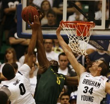 Rick Egan    The Salt Lake Tribune   Brandon Davies blocks a shot by Oregon's Olu Ashaolu (5)as Noah Hartsock helps out for the Cougars, in first half basketball action, BYU vs Oregon, at EnergySolutions Arena, Saturday, December 3, 2011.
