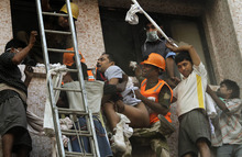 Fire officials rescue a patient from the window of a hospital after it caught fire in Kolkata, India, Friday, Dec. 9, 2011. The fire swept through the multistory hospital in eastern India early Friday, trapping many elderly patients in the smoke-filled building, an official said. (AP Photo/Bikas Das)