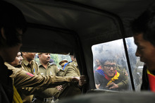 Indian policemen detain an exile Tibetan during a protest, in New Delhi, India, Friday, Dec. 9, 2011. Tibetan activists protested the visit of China's Deputy Chief of General Staff General Ma Xiaotian. Xiatian is on a two-day visit to India. (AP Photo/Tsering Topgyal)