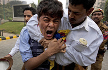An Indian hotel employee holds down an exile Tibetan during a protest rally in New Delhi, India, Friday, Dec. 9, 2011. Tibetan activists protested the visit of China's Deputy Chief of General Staff General Ma Xiaotian. Xiatian is on a two-day visit to India. (AP Photo/Manish Swarup)