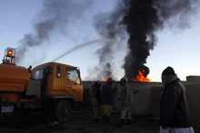 Pakistani fire fighters try to extinguish burning NATO oil tankers after they were allegedly torched by militants at a terminal on the outskirts of Quetta, Pakistan on Friday, Dec. 9, 2011. Assailants torched more than 20 tankers in Pakistan carrying fuel for U.S. and NATO troops in neighboring Afghanistan, the first reported attack since Islamabad closed the border to protest coalition airstrikes that killed 24 Pakistani troops last month. (AP Photo/Arshad Butt)