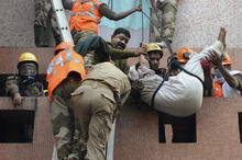 Rescue workers use ropes to evacuate people after a fire engulfed a hospital, in Kolkata, India, Friday, Dec. 9, 2011. A fire swept through a hospital in the Indian city of Kolkata early Friday, trapping many and sending emergency workers scrambling to evacuate patients and medical staff from the smoke-filled building, officials said. (AP Photo)