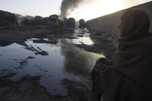 A Pakistani watches burnt-down NATO oil tankers after they were allegedly torched by militants at a terminal on the outskirts of Quetta, Pakistan on Friday, Dec. 9, 2011. Assailants torched more than 20 tankers in Pakistan carrying fuel for U.S. and NATO troops in neighboring Afghanistan, the first reported attack since Islamabad closed the border to protest coalition airstrikes that killed 24 Pakistani troops last month. (AP Photo/Arshad Butt)