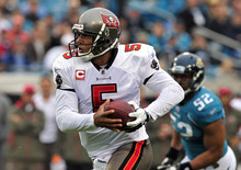 Tampa Bay Buccaneers quarterback Josh Freeman (5) runs past Jacksonville Jaguars outside linebacker Daryl Smith (52) for a 13-yard touchdown during the first half of an NFL football game on Sunday, Dec. 11, 2011, in Jacksonville, Fla. (AP Photo/Stephen Morton)