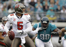Tampa Bay Buccaneers quarterback Josh Freeman (5) looks for a receiver as he is pressured by Jacksonville Jaguars defensive tackle Nate Collins (98) during the first half of an NFL football game on Sunday, Dec. 11, 2011, in Jacksonville, Fla. (AP Photo/John Raoux)