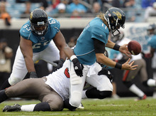 Jacksonville Jaguars quarterback Blaine Gabbert (11) fumbles the ball as he is tackled by Tampa Bay Buccaneers defensive end Adrian Clayborn during the first half of an NFL football game on Sunday, Dec. 11, 2011, in Jacksonville, Fla.  (AP Photo/Phelan M. Ebenhack)