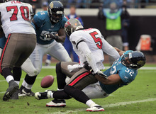 Jacksonville Jaguars outside linebacker Daryl Smith (52) tackles Tampa Bay Buccaneers quarterback Josh Freeman (5) on the goal line to force a fumble during the first half of an NFL football game on Sunday, Dec. 11, 2011, in Jacksonville, Fla. (AP Photo/Stephen Morton)