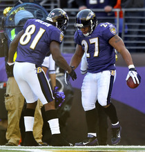 Baltimore Ravens wide receiver Anquan Boldin, left, shakes hands with Ravens running back Ray Rice after Rice scored a touchdown in the first half of an NFL football game against the Indianapolis Colts in Baltimore, Sunday, Dec. 11, 2011. (AP Photo/Gail Burton)