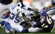 Baltimore Ravens defender Edgar Jones, right, tackles Indianapolis Colts' Joe Lefeged in the first half of an NFL football game in Baltimore, Sunday, Dec. 11, 2011. (AP Photo/Nick Wass)