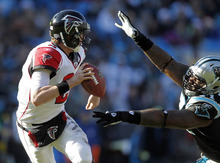 Atlanta Falcons' Matt Ryan, left, scrambles under pressure from Carolina Panthers' Jason Shirley, right, during the second quarter of an NFL football game in Charlotte, N.C., Sunday, Dec. 11, 2011. (AP Photo/Bob Leverone)