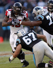 Atlanta Falcons' Mike Peterson (53) returns an interception as Carolina Panthers'  Ryan Kalil (67) and Mackenzy Bernadeau (73) defend during the third quarter of an NFL football game in Charlotte, N.C., Sunday, Dec. 11, 2011. (AP Photo/Nell Redmond)