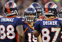 Denver Broncos quarterback Tim Tebow (15) stands in the huddle with wide receiver Demaryius Thomas (88) and wide receiver Eric Decker (87) after a touchdown by the Chicago Bears in the third quarter of an NFL football game, Sunday, Dec. 11, 2011, in Denver. (AP Photo/Joe Mahoney)