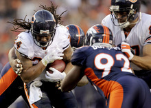Chicago Bears running back Marion Barber (24) is hit by Denver Broncos defensive tackle Marcus Thomas, rear, and defensive end Elvis Dumervil (92) on his way to a first down in the third quarter of an NFL football game, Sunday, Dec. 11, 2011, in Denver. (AP Photo/Joe Mahoney)