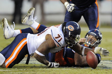 Chicago Bears defensive end Israel Idonije (71) recovers a fumble by Denver Broncos quarterback Tim Tebow (15) in the fourth quarter of an NFL football game, Sunday, Dec. 11, 2011, in Denver. (AP Photo/Jack Dempsey)