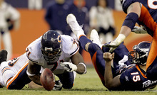 Chicago Bears defensive end Israel Idonije (71) hits Denver Broncos quarterback Tim Tebow (15), causing him to fumble the ball in the fourth quarter of an NFL football game, Sunday, Dec. 11, 2011, in Denver. Idonije recovered the fumble on the play. (AP Photo/Joe Mahoney)