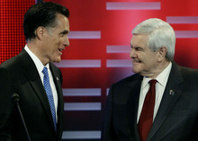 Republican presidential candidates former Massachusetts Gov. Mitt Romney, left, and former Speaker of the House Newt Gingrich, right, talk during a break in the Republican debate, Saturday, Dec. 10, 2011, in Des Moines, Iowa. Attacked as a lifelong Washington insider,  Gingrich parried criticism from Mitt Romney Saturday night, telling the former Massachusetts governor,