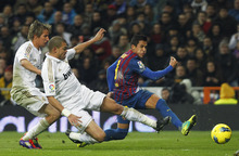 Real Madrid's Coentrao, left, and Pepe from Portugal, center, vies for the ball with FC Barcelona's Alexis Sanchez from Chile, right, during their Spanish La Liga soccer match at the Santiago Bernabeu stadium in Madrid, Spain, Saturday, Dec. 10, 2011. (AP Photo/Andres Kudacki)