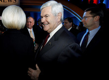 Republican presidential candidate, former Speaker of the House Newt Gingrich, center, leaves with his wife, Callista, left, following the Republican debate, Saturday, Dec. 10, 2011, in Des Moines, Iowa. Attacked as a lifelong Washington insider,  Gingrich parried criticism from Mitt Romney Saturday night, telling the former Massachusetts governor,