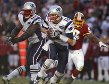 New England Patriots quarterback Tom Brady (12) avoids the Washington Redskins pass rush during the first half of an NFL football game on Sunday, Dec. 11, 2011, in Landover, Md.  (AP Photo/Evan Vucci)