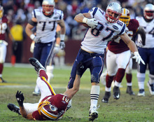 New England Patriots tight end Rob Gronkowski (87) breaks away from Washington Redskins outside linebacker Ryan Kerrigan (91) for a touchdown during the second half of an NFL football game on Sunday, Dec., 11, 2011, in Landover, Md. (AP Photo/Rich Lipski)