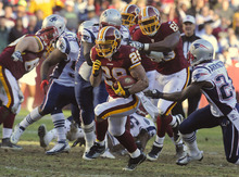 Washington Redskins running back Roy Helu (29) is chased by New England Patriots cornerback Kyle Arrington (24), right, during the first half of an NFL football game on Sunday, Dec. 11, 2011, in Landover, Md.  (AP Photo/Rich Lipski)