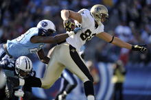 New Orleans Saints tight end Jimmy Graham (80) carries the ball against Tennessee Titans defenders Anthony Smith (25) and Chris Hope (24) in the second quarter of an NFL football game on Sunday, Dec. 11, 2011, in Nashville, Tenn. (AP Photo/Joe Howell)