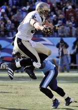 New Orleans Saints tight end Jimmy Graham, top, is hit by Tennessee Titans safety Chris Hope, bottom, in the second quarter of an NFL football game on Sunday, Dec. 11, 2011, in Nashville, Tenn. (AP Photo/Frederick Breedon)
