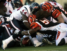 Houston Texans running back Ben Tate (44) fumbles the ball as he is hit by Cincinnati Bengals linebackers Rey Maualuga (58) and Dan Skuta (51) in the first half of an NFL football game on Sunday, Dec. 11, 2011, in Cincinnati. Cincinnati recovered the fumble. (AP Photo/Tony Tribble)