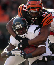 Cincinnati Bengals defensive end Michael Johnson (93) tackles Houston Texans running back Ben Tate after a short gain in the first half of an NFL football game on Sunday, Dec. 11, 2011, in Cincinnati. (AP Photo/Tony Tribble)