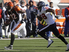 Cincinnati Bengals running back Cedric Benson (32) runs past Houston Texans safety Danieal Manning (38) in the first half of an NFL football game on Sunday, Dec. 11, 2011, in Cincinnati. (AP Photo/David Kohl)