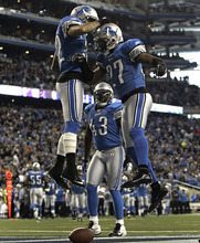 Detroit Lions defensive back Alphonso Smith (27) celebrates his 30-yard interception for a touchdown with defensive back Aaron Berry (32) as teammate Chris Harris (43) looks on during the second quarter of an NFL football game against the Minnesota Vikings in Detroit, Sunday, Dec. 11, 2011. (AP Photo/Paul Sancya)