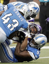 Minnesota Vikings wide receiver Percy Harvin, center, is tackled by Detroit Lions defensive tackle Corey Williams, top, strong safety Chris Harris (43) and defensive end Cliff Avril (92) in the first half of an NFL football game on Sunday, Dec. 11, 2011, in Detroit. (AP Photo/Duane Burleson)