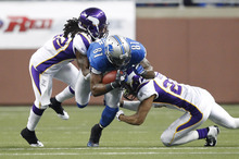 Detroit Lions wide receiver Calvin Johnson (81) is stopped by Minnesota Vikings cornerback Cedric Griffin, left, and defensive back Benny Sapp (22) during the first quarter of an NFL football game in Detroit, Sunday, Dec. 11, 2011. (AP Photo/Rick Osentoski)