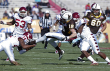 Wyoming wide receiver Brandon Miller (18) is tackled by Temple defensive back Vaughn Carraway (14) and linebacker Tahir Whitehead (2) in the first quarter of the New Mexico Bowl NCAA college football game in Albuquerque, N.M., Saturday, Dec. 17, 2011. (AP Photo/Jake Schoellkopf)