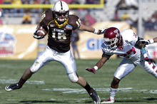 Wyoming quarterback Brett Smith (16) breaks away from Temple defensive back Zamel Johnson (27) in the first quarter of the New Mexico Bowl NCAA college football game in Albuquerque, N.M., Saturday, Dec. 17, 2011. (AP Photo/Jake Schoellkopf)