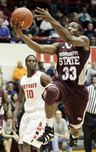 Mississippi State guard Deville Smith (33) goes to the basket past Detroit guard Jason Calliste (10) in the first half of an NCAA college basketball game Saturday, Dec. 17, 2011, in Detroit. (AP Photo/Duane Burleson)