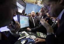 Fashion designer Michael Kors, background center, watches as trader Dudley Devine, left, and specialist Patrick Murphy, right, confer before the IPO of Michael Kors Holdings Ltd. begins trading on the floor of the New York Stock Exchange, Thursday, Dec. 15, 2011. The designer's company raised $944 million after selling 47.2 million shares in its initial public stock offering Wednesday night, valuing the company at $3.8 billion. (AP Photo/Richard Drew)