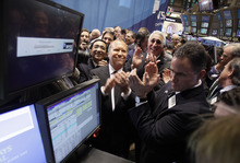 Richard Drew  |  The Associated Press Fashion designer Michael Kors, center, applauds with Silas K. F. Chou, left, and Lawrence S. Stroll, third left, as the IPO of Michael Kors Holdings Ltd, begins trading on the floor of the New York Stock Exchange, Thursday, Dec. 15, 2011. The designer's company raised $944 million after selling 47.2 million shares in its initial public stock offering Wednesday night, valuing the company at $3.8 billion.