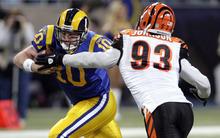 St. Louis Rams quarterback Kellen Clemens, left, scrambles for a 1-yard gain as Cincinnati Bengals defensive end Michael Johnson defends during the third quarter of an NFL football game Sunday, Dec. 18, 2011, in St. Louis. (AP Photo/Tom Gannam)