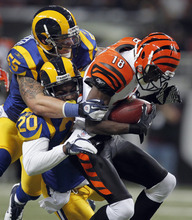 Cincinnati Bengals wide receiver A.J. Green, right, is brought down by St. Louis Rams linebacker James Laurinaitis (55) and Darian Stewart (20) after catching a pass for a 30-yard gain during the first quarter of an NFL football game Sunday, Dec. 18, 2011, in St. Louis. (AP Photo/Jeff Roberson)