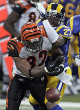 Cincinnati Bengals running back Cedric Benson, front, fumbles the ball as he is hit by St. Louis Rams safety Quintin Mikell during the third quarter of an NFL football game Sunday, Dec. 18, 2011, in St. Louis. Benson recovered the fumble. (AP Photo/Tom Gannam)