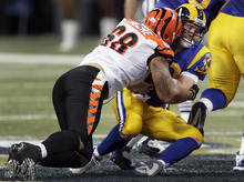 St. Louis Rams quarterback Kellen Clemens, right, is sacked for a 6-yard loss by Cincinnati Bengals defensive end Jonathan Fanene during the second quarter of an NFL football game Sunday, Dec. 18, 2011, in St. Louis. (AP Photo/Tom Gannam)