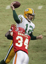 Green Bay Packers quarterback Aaron Rodgers (12) throws under pressure from Kansas City Chiefs defensive back Travis Daniels (34) during the second half of an NFL football game at Arrowhead Stadium in Kansas City, Mo., Sunday, Dec. 18, 2011. (AP Photo/Charlie Riedel)