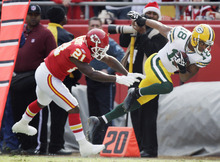 Green Bay Packers wide receiver Randall Cobb (18) is forced out of bounds by Kansas City Chiefs defensive back Javier Arenas (21) during the first half of an NFL football game at Arrowhead Stadium in Kansas City, Mo., Sunday, Dec. 18, 2011. (AP Photo/Ed Zurga)